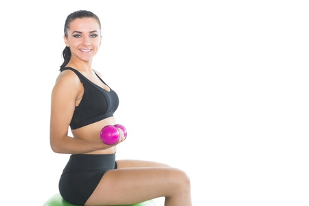 Beautiful slim woman using pink dumbbells sitting on an exercise ball smiling at camera photo