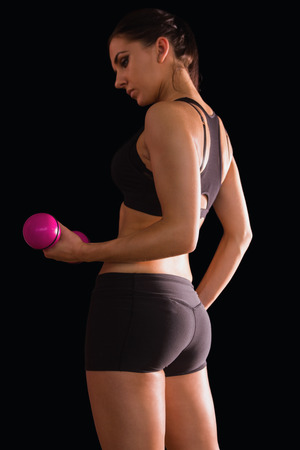 Active young woman lifting a pink dumbbell on black background photo