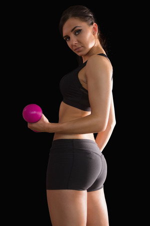 Portrait of beautiful fit woman lifting a pink dumbbell on black background photo