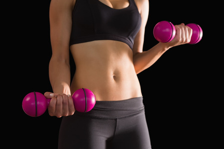 Slender active woman lifting pink dumbbells on black background Stock Photo - 25779808