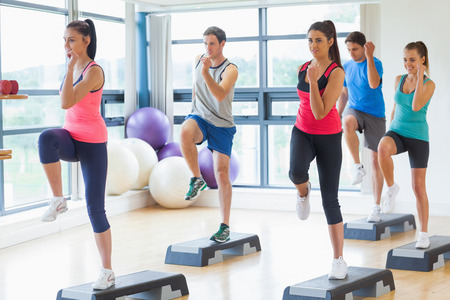exercise room: Full length of instructor with fitness class performing step aerobics exercise in gym Stock Photo
