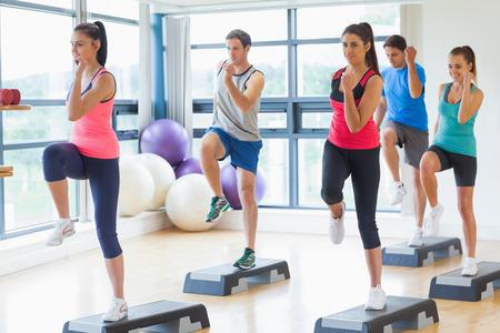 ejercicio aer�bico: Longitud total de instructor con el ejercicio paso clase de fitness en el gimnasio realizando ejercicios aer�bicos