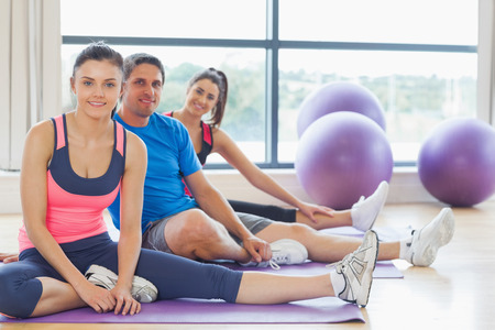 Portrait of smiling class and instructor sitting on exercise mats in fitness studio photo