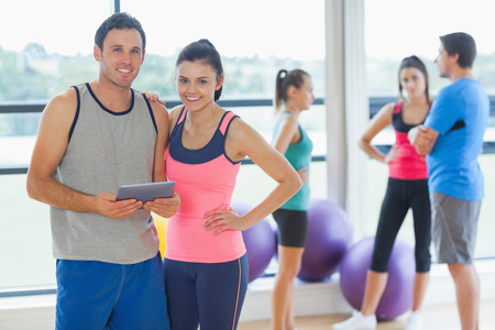 Fit couple holding digital table with friends chatting in background in bright exercise room photo