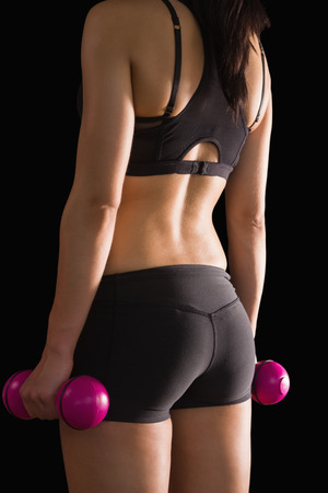 Rear view of slender woman holding pink dumbbells on black background Stock Photo - 25781146