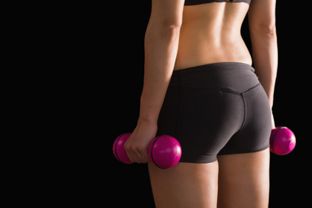 Rear view of slim woman wearing sportswear holding pink dumbbells on black background photo