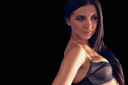 Gorgeous brunette woman wearing dark lingerie posing on black background photo
