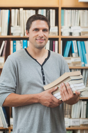 Mature student posing in library holding a pile of books smiling at camera photo