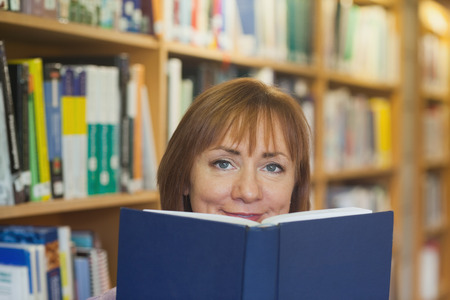 Peaceful mature woman holding a book in a library looking at camera photo