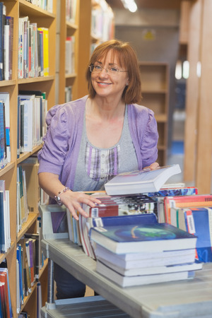 returning: Female mature librarian returning books in library smiling at camera Stock Photo