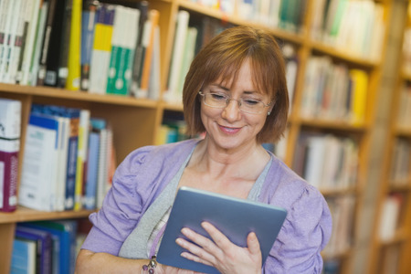 Content mature librarian using her tablet standing in a library photo