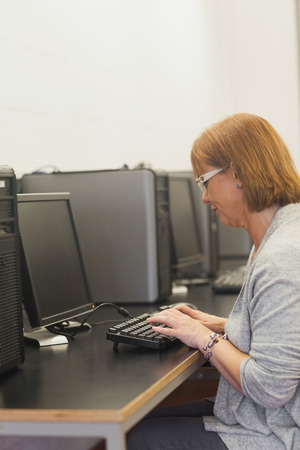 Focused mature student sitting in computer class working with a computer photo