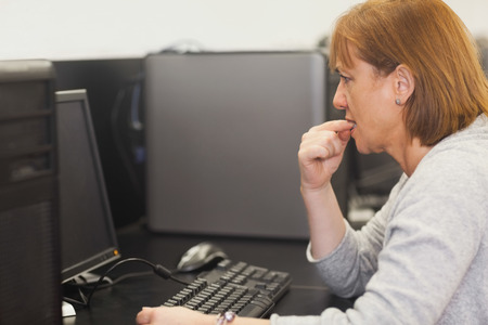 Unsure female mature student working on computer in computer class photo