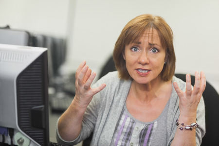 Outraged mature student sitting in front of computer looking at camera photo