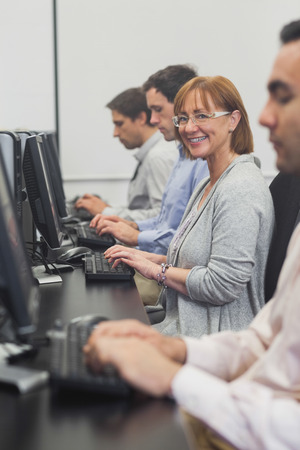 Female mature student sitting in computer class smiling at camera photo