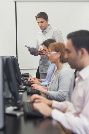 Teacher standing in front of computer class in college photo