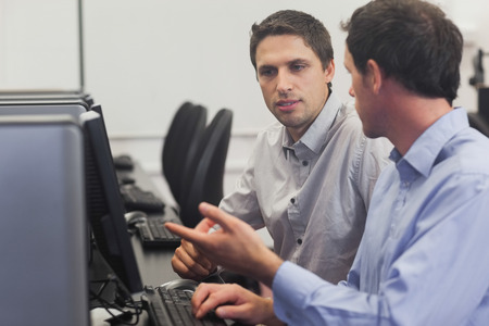 Two attractive men talking in computer class pointing at monitor photo