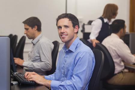 attractive male: Estudiante masculino atractivo que se sienta en clase del ordenador sonriendo a la c�mara Foto de archivo