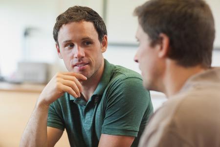 amigas conversando: Dos estudiantes maduros hermoso que tiene una conversación sentado en la sala de clases Foto de archivo