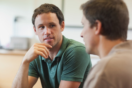 Two handsome mature students having a conversation sitting in class room
