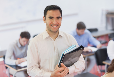 Portrait of handsome teacher posing in his classroom while holding some files photo