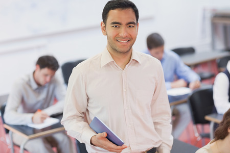 Cheerful male teacher posing in his classroom holding a tablet smiling at camera photo