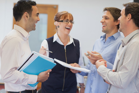 adult classroom: Group of mature students standing in classroom chatting and laughing