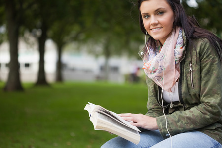 gleeful: Gleeful brunette student sitting on bench reading on campus at college Stock Photo
