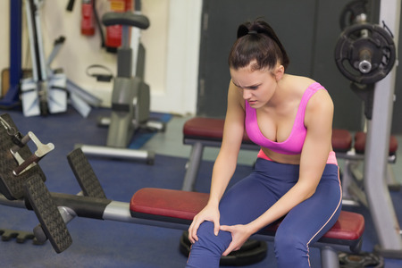 Healthy young woman with an injured knee sitting in the gym photo