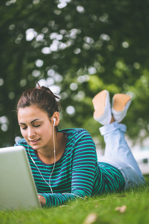Content casual student lying on grass using laptop on campus at college photo
