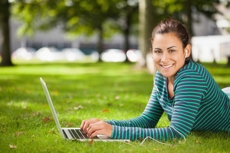 Attractive casual student lying on grass using laptop looking at camera on campus at college photo