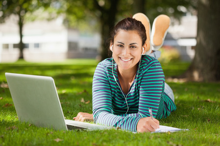 Happy casual student lying on grass taking notes on campus at college photo