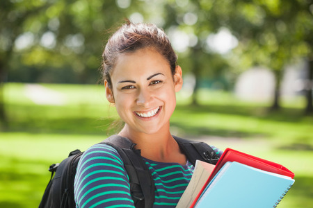 Casual cheerful student holding books on campus at college photo
