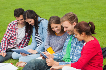 Five students sitting on the grass using tablet on campus at college photo