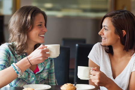 school friends: Two smiling students having a cup of coffee in college canteen Stock Photo