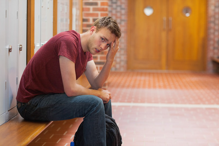 gloominess: Frowning handsome student having a headache in school Stock Photo