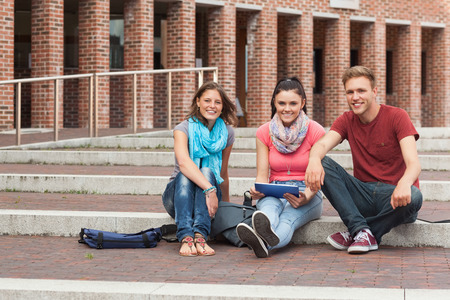 Smiling students sitting on stairs holding tablet in school photo
