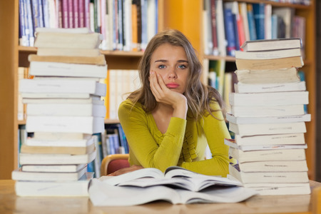 Exhausted pretty student studying between piles of books in library photo