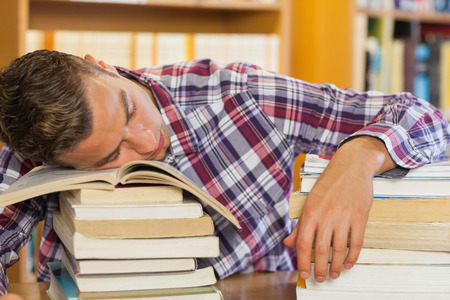 revising: Tired handsome student resting head on piles of books in library Stock Photo