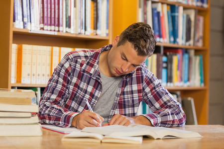 noting: Handsome concentrated student studying his books in library
