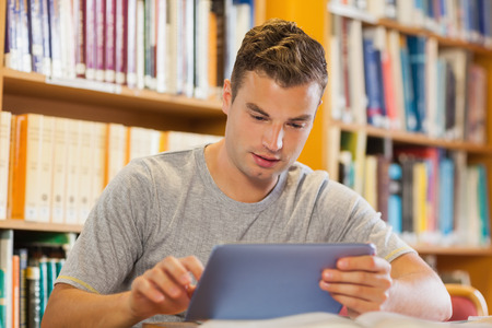 Attractive casual student using tablet in library photo