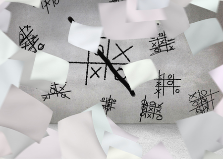 White paper in front of grey wall with tictactoe photo