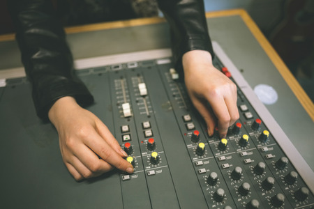 Close up of female hands turning up volume in radio studio at college photo
