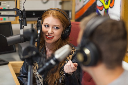 radio station: Attractive happy radio host interviewing a guest in studio at college