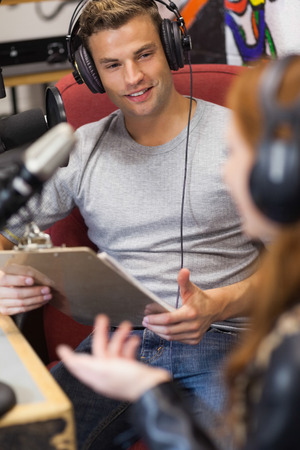 Attractive radio host interviewing a guest holding clipboard in studio at college