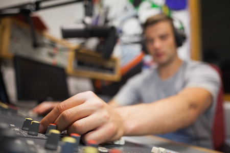Handsome radio host moderating touching switch in studio at college photo