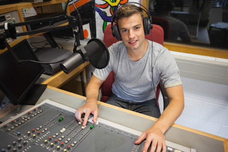 Handsome cheerful radio host moderating sitting in studio at college photo