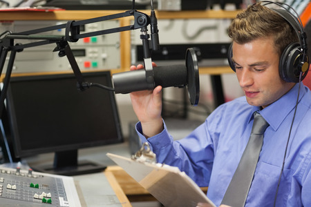 sound recording equipment: Well dressed focused radio host moderating sitting in studio at college Stock Photo