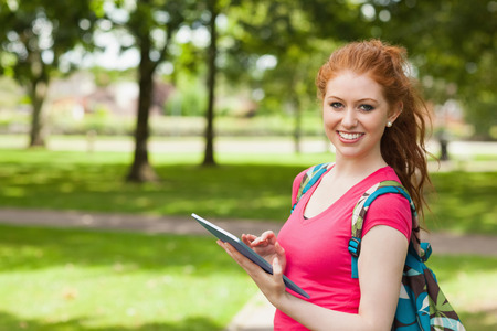 Gorgeous smiling student using tablet on campus at college photo