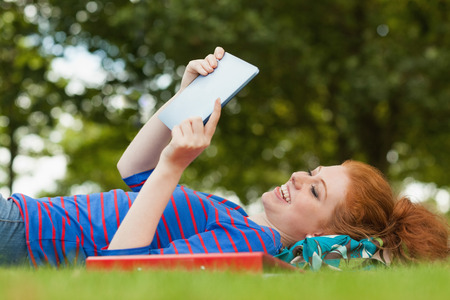 revising: Gorgeous smiling student lying on grass using tablet on campus at college Stock Photo